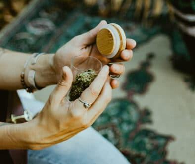 woman's hand holding a hakuna jar and hemp flower