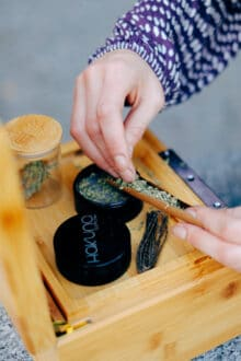 womans hand filling a blunt with cannabis flower with a stash box, grinder and stash jar in the background.